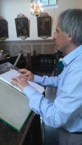 Mann an einem Pult, der einen Text in Blindenschrift vorliest