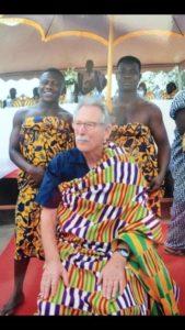 Prof. Spitznas sitzt in ein traditionelles Gewand der Akan Völker gekleiet, während hinter ihm links und rechts zwei Mitglieder der Akan Völker, ebenfalls in Gewandung, stehen.